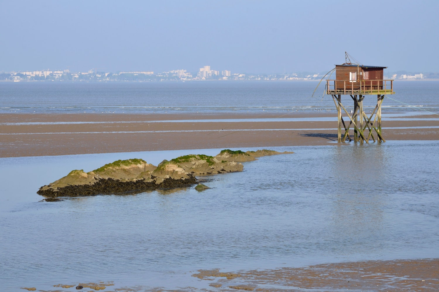 24836074 - fishing carrelet from saint brevin les pins at low tide and the town